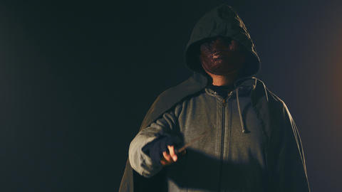Killer gestures throat cut monster mask and cloak hoodie swings knife Live Action