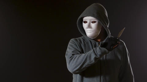 Killer in white mask and hoodie with knife walks past camera Live Action