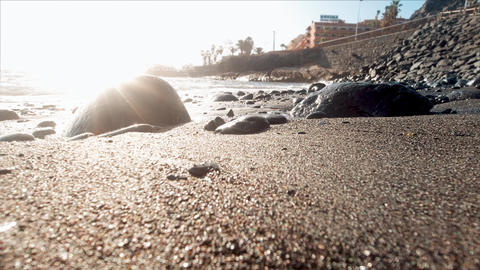Closeup 4k video of calm sandy sea beach with big rocks and cliffs in sunset Live Action