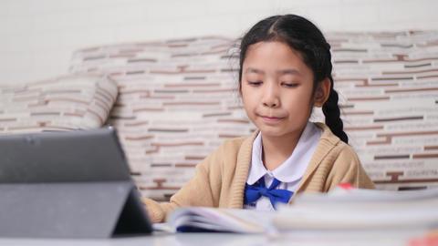Little Asian girl doing homework with happiness, Thai girl in student kindergarten uniform, learning Live Action