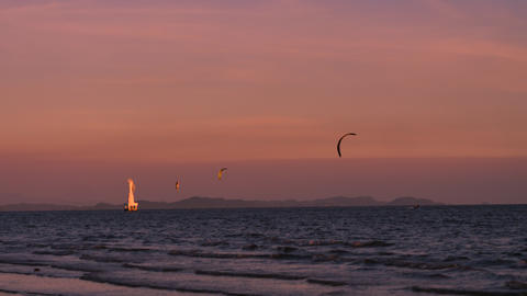 Scenic landscape of twilight beach in summer in Thailand, with beacon tower and people playing Live Action