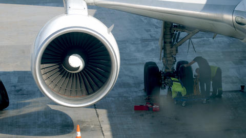 4k video of group of land crew in airport repairing chassis on passenger jet Live Action