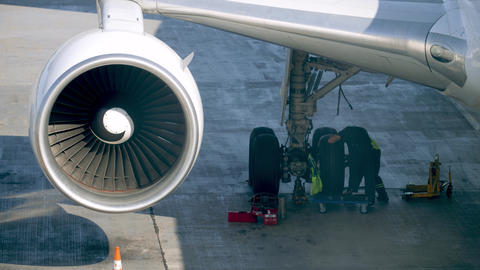 4k video of two mechanics reapiring airplane before flight. Aircraft maintenance Live Action