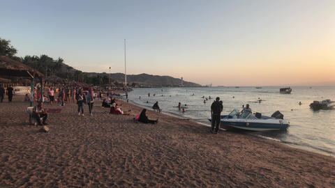 Aqaba, Jordan - October 15, 2019: tourists on the evening beach of the red sea Live Action