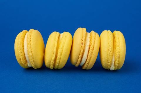 yellow lemon round baked macaroon cakes on a dark blue backgroun Fotografía