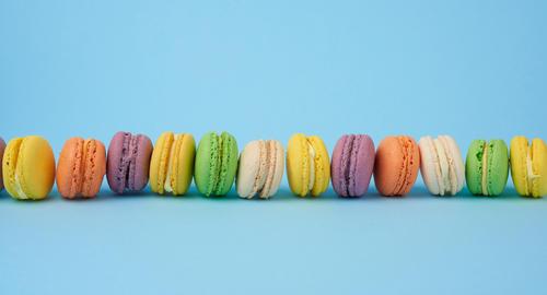 many multi-colored round baked macarons cakes on a light blue ba Fotografía