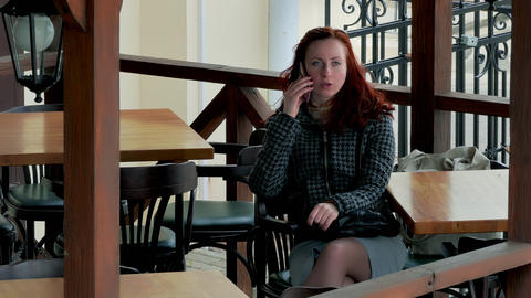 1080p Girl Speaks on Cell Phone at Table in Empty Outdoor Cafe When The Footage