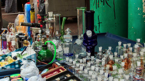 Man Arranges Hookahs Jars on Mobile Counter in Street Footage