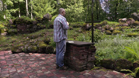 Man praying at the altar in outdoor church Footage