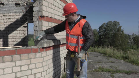Construction worker with sledgehammer beats brick wall Footage