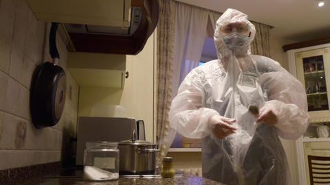 Woman wearing protective suit cooking at kitchen GIF