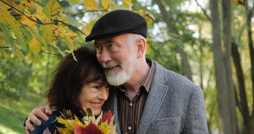 Front shot of a happy and cheerful elderly couple in a cozy city park in the Live Action