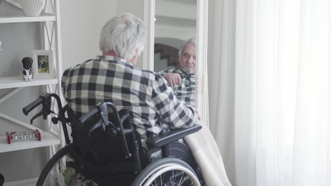 Close-up back view of mature Caucasian man in wheelchair looking at his Live Action