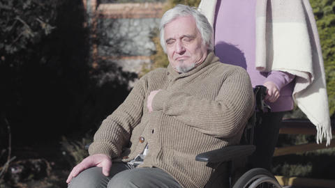 Portrait of tired elderly Caucasian disabled man sitting on wheelchair outdoors Live Action