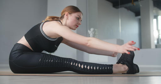 Attractive young woman stretches herself by bending forward in sitting position Live Action