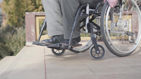 Side view close-up of wheelchair with unrecognizable old man rolling to stairs Live Action