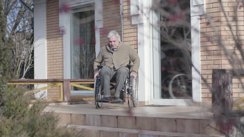 Old Caucasian man in wheelchair rolling to stairs without ramp outdoors and Live Action