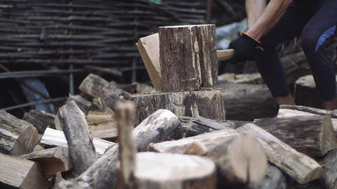 Man chops wood outdoors in slow motion. Man's hands working with ax. A man Live Action