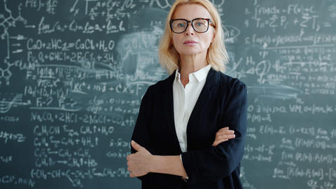 Portrait of serious smart lady professor in classroom with formulas on Live Action