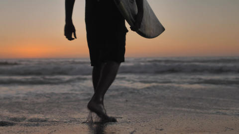 Person with surfboard walks towards waves Live Action