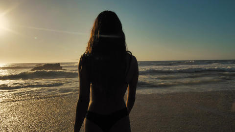 Woman walking towards the ocean Live Action