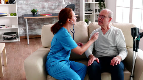 Female young nurse using stethoscope in nursing home Live Action