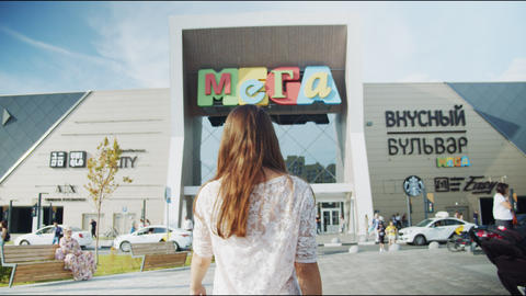 young lady in white lacy blouse walks to Mega shopping mall Live Action