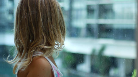 Little blonde girl is standing, turned to transparent glass Live Action