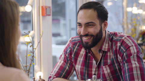 Portrait of positive Middle Eastern bearded man laughing out loud at jokes of Live Action