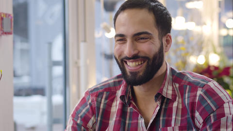 Close-up face of cheerful Middle Eastern man laughing out loud and drinking tea Live Action