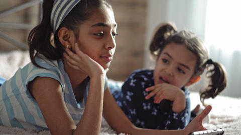 Two middle eastern young girls on the bed with a smartphone. Two dark-skinned Live Action