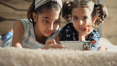 Two middle eastern young girls on the bed with a smartphone. Two swarthy sisters Live Action