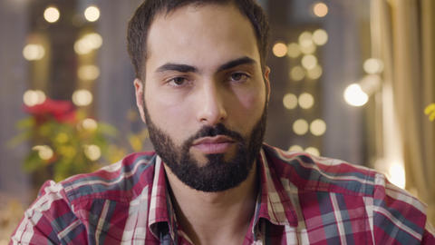 Close-up portrait of confident handsome Middle Eastern man with black hair and Live Action