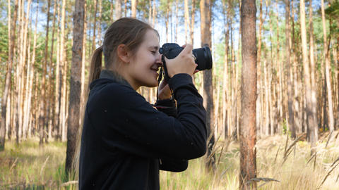 4k video of young female wildlife photographer making images of nature while Live Action