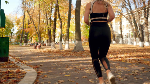 Closeup 4k video of female feet in sneakers while running on path at autumn park Live Action