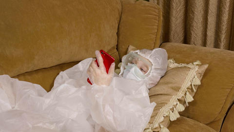 Teenager girl in protective costume and mask looking smartphone on couch. Girl Live Action