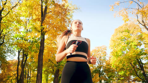 4k video from low point of view on young beautiful woman running at autumn park Live Action