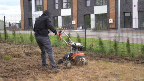 skilled worker man loosens soil with manual tractor in house yard. Gimbal shot Live Action