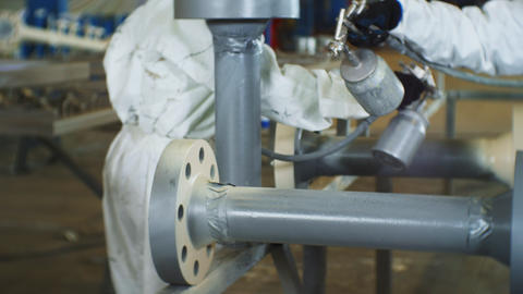 workers paint pipes with sprayers in plant workshop closeup Live Action