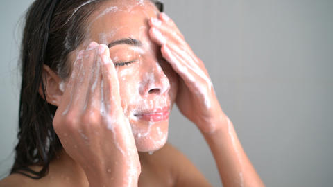 Skincare woman washing face in shower foaming facewash soap on skin Live Action
