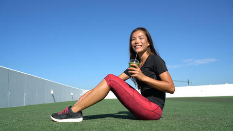 Fitness woman drinking healthy green smoothie after workout exercises Live Action