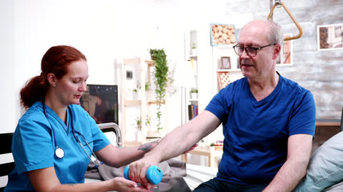 Female doctor helping retired man with his exercise Live Action