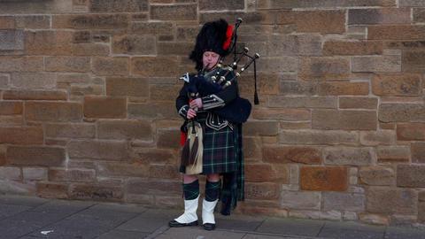 Bagpipe musician in the streets of Edinburgh - EDINBURGH, SCOTLAND - JANUARY 10 Live Action