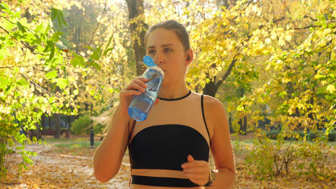 Portrait of beautiful smiling young woman running at park and drinking water Live Action