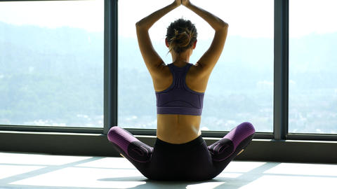 Woman doing stretching near a large window in a yoga room Live Action