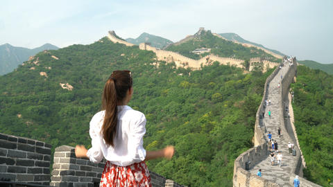 Happy cheering tourist woman at Great Wall of China having fun arms outstretched Live Action