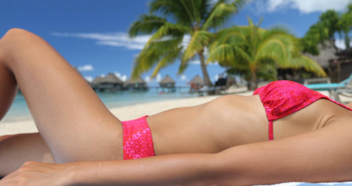 Sunbathing young woman on relaxing on beach in bikini on vacation beach travel Live Action