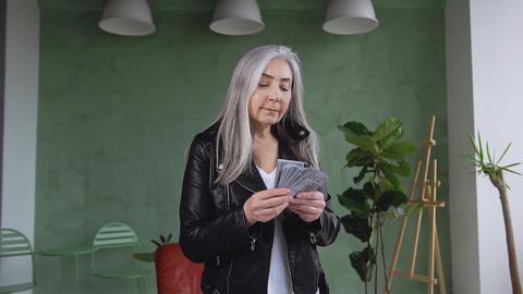 Front view of satisfied rich fashion 60-aged woman with long gray hair which Live Action
