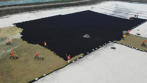 laborers in orange vests put sand on black plastic grid Live Action