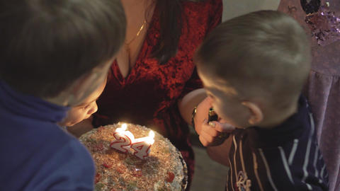 Children blow out the candles on the cake. Three boys blow out the candles on Live Action